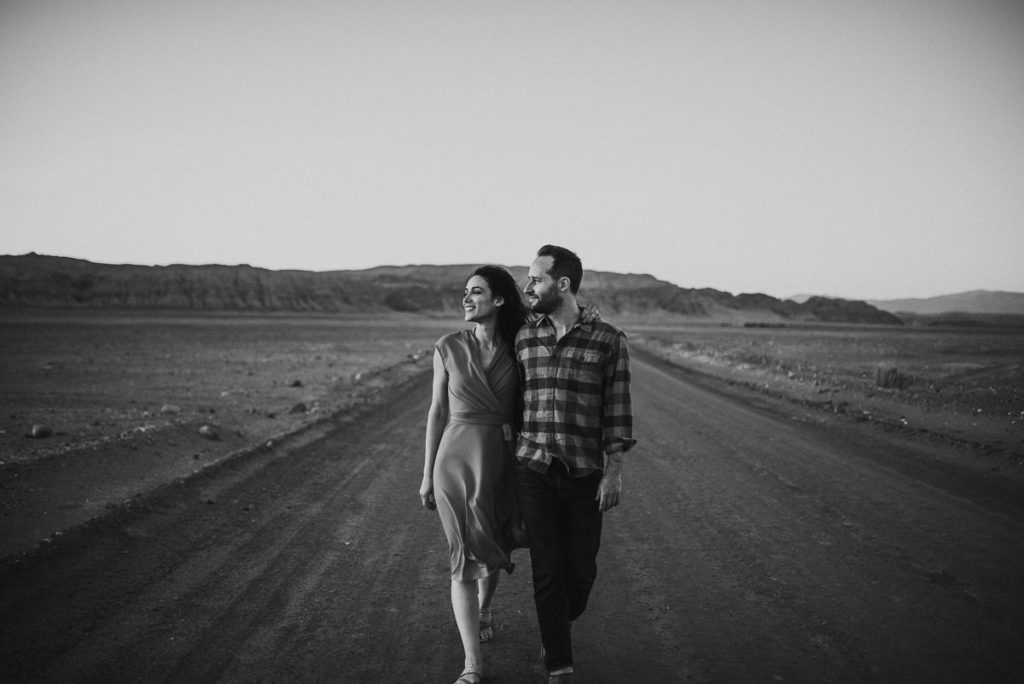 Couple walking along the highway in the desert during their adventure engagement session