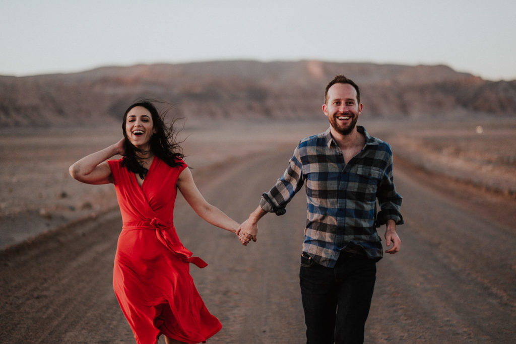 Couple laughing and walking along the desert during their destination adventure engagement session with Carey Nash